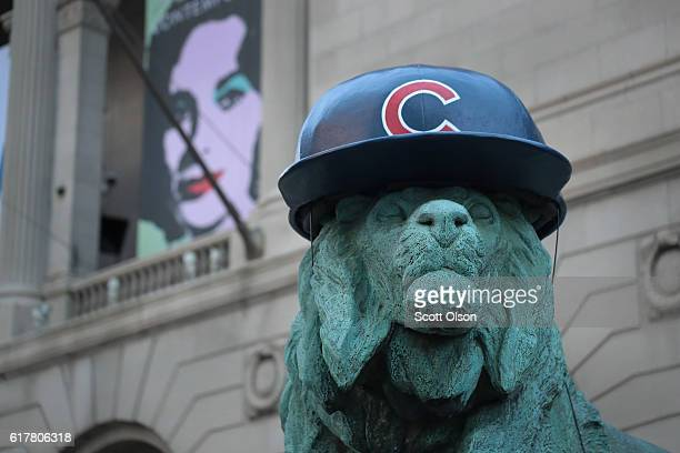 A lion sculpture outside the Art Institute of Chicago wears a batting helmet to help the city celebrate the Chicago Cubs making it into the World...