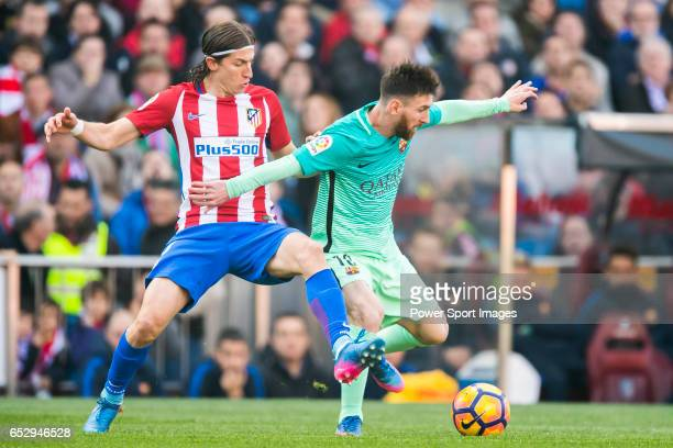 Lionel Andres Messi of FC Barcelona fights for the ball with Filipe Luis of Atletico de Madrid during their La Liga match between Atletico de Madrid...