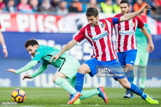 Lionel Andres Messi of FC Barcelona fights for the ball with Gabriel Fernandez Arenas Gabi of Atletico de Madrid during their La Liga match between...