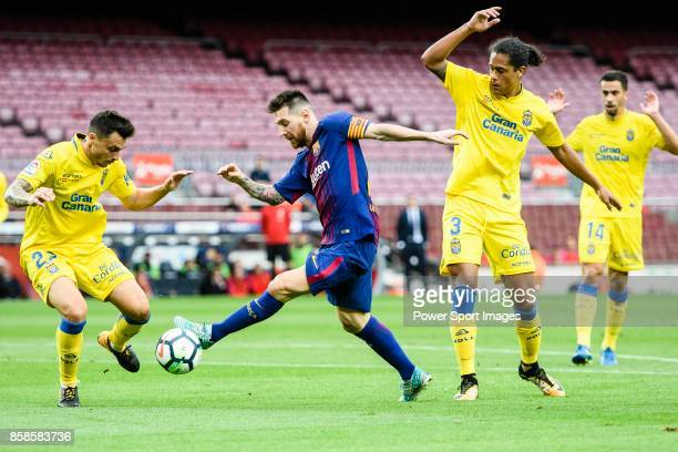 Lionel Andres Messi of FC Barcelona fights for the ball with Mauricio Lemos of UD Las Palmas and Ximo Navarro Jimenez of UD Las Palmas during the La...