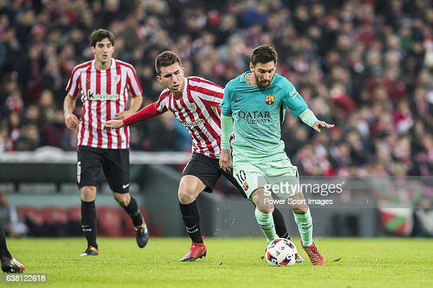Lionel Andres Messi of FC Barcelona is followed by Aymeric Laporte of Athletic Club during their Copa del Rey Round of 16 first leg match between...