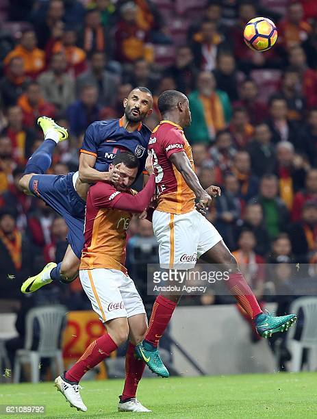 Lionel Carol and Sinan Gumus of Galatasaray in action against Yalcin Ayhan of Medipol Basaksehir during the Turkish Spor Toto Super League soccer...