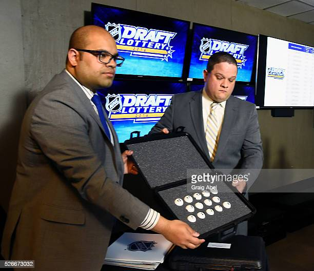 Lionel Coutinho of Ernst and Young and Douglas Hogancamp of Smartplay open the sealed case of lottery balls during The National Hockey League Draft...