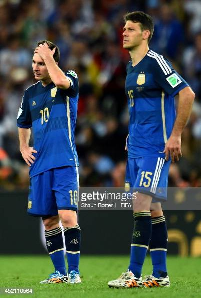 Lionel Messi and Martin Demichelis of Argentina react after the 01 defeat in the 2014 FIFA World Cup Brazil Final match between Germany and Argentina...