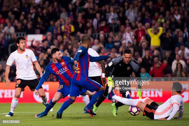 Lionel Messi and Rafinha of FC Barcelona try to score under pressure from Dani Parejo goalkeeper Diego Alves and Fabian Orellana of Valencia CF...