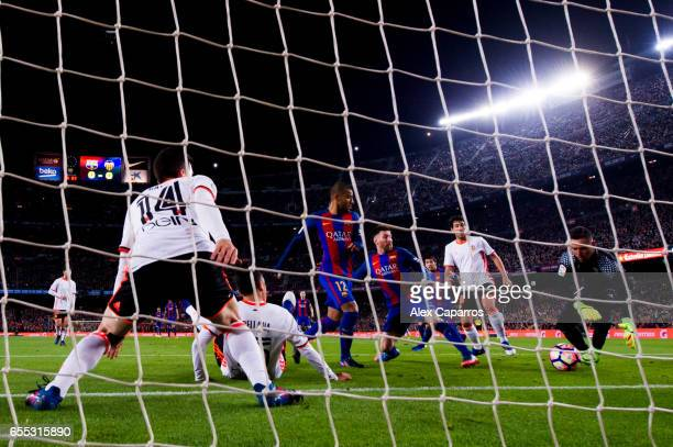 Lionel Messi and Rafinha of FC Barcelona try to score under pressure from Jose Luis Gaya Fabian Orellana Dani Parejo and goalkeeper Diego Alves of...