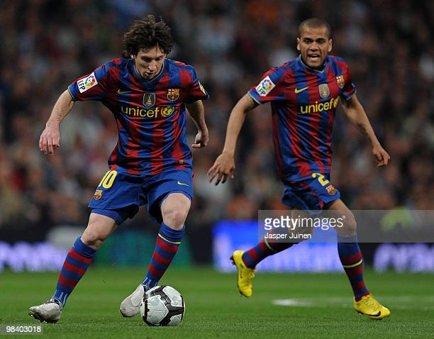 Lionel Messi controls the ball flanked by his teammate Daniel Alves of FC Barcelona during the La Liga match between Real Madrid and Barcelona at the...