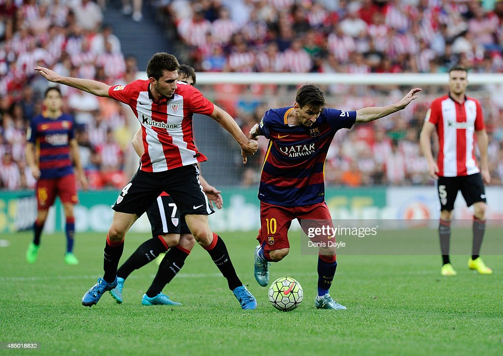 Lionel Messi is defended by Aymeric Laporte of Athletic Club at the end of the La Liga match between Athletic Club and FC Barcelona at San Mames...