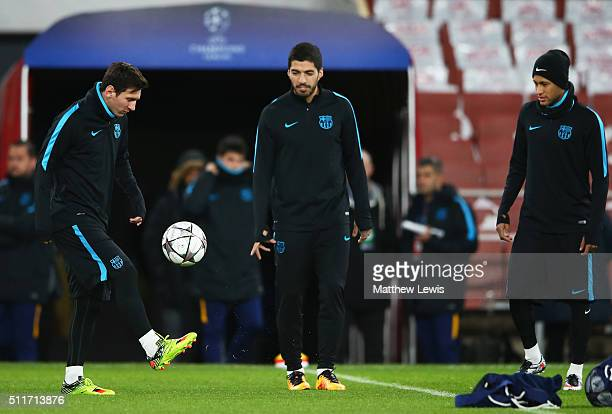 Lionel Messi is watched by team mates Luis Suarez and Neymar during a FC Barcelona training session ahead of their UEFA Champions League round of 16...