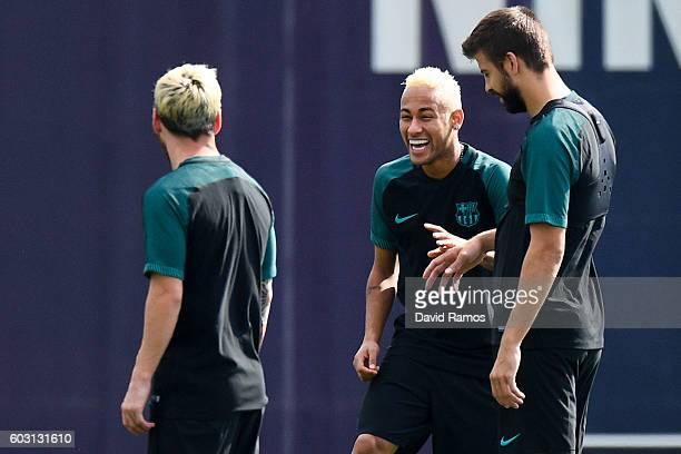 Lionel Messi Neymar Jr and Gerard Pique of FC Barcelona share a joke during a training session ahead of their UEFA Champions League Group C match...