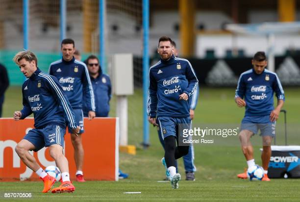Lionel Messi of Argentina and Lucas Biglia run during a training session at Argentine Football Association 'Julio Humberto Grondona' training camp on...