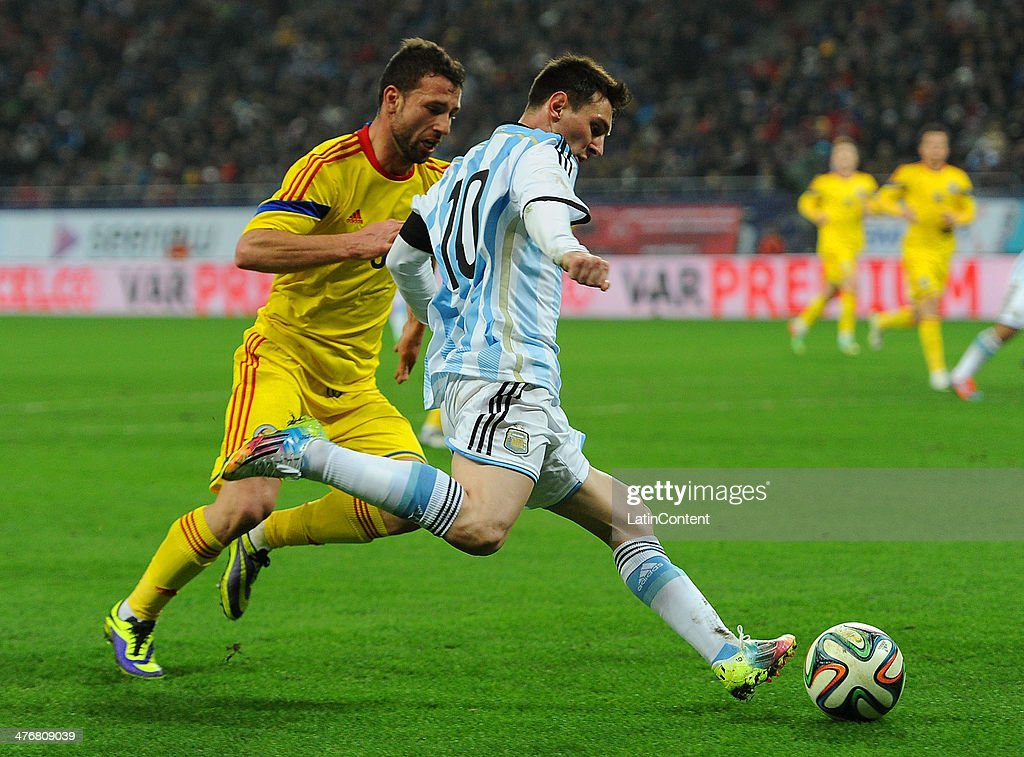 <a gi-track='captionPersonalityLinkClicked' href=/galleries/search?phrase=Lionel+Messi&family=editorial&specificpeople=453305 ng-click='$event.stopPropagation()'>Lionel Messi</a> (R) of Argentina and <a gi-track='captionPersonalityLinkClicked' href=/galleries/search?phrase=Razvan+Rat&family=editorial&specificpeople=2147212 ng-click='$event.stopPropagation()'>Razvan Rat</a>-Dinca (L) of Romania in action during a friendly match between Romania and Argentina at Arena Nationala Stadium on March 05, 2014 in Bucharest, Romania.