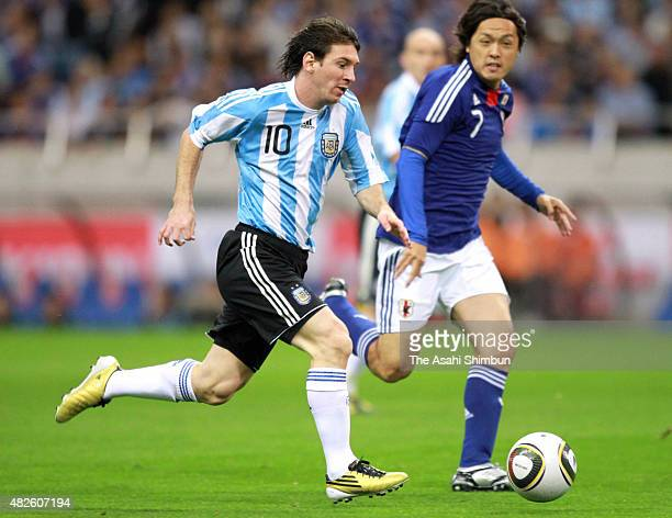 Lionel Messi of Argentina and Yasuhito Endo of Japan compete for the ball during the international friendly match between Japan and Argentina at...