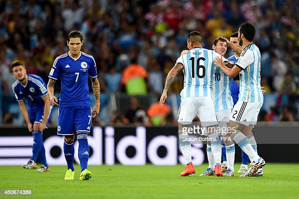 Lionel Messi of Argentina celebrates with Marcos Rojo of Argentina as Muhamed Besic of Bosnia and Herzegovina looks on dejected following Sead...