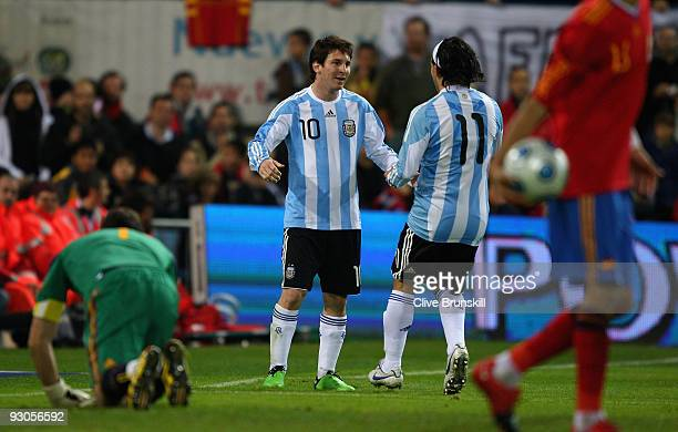Lionel Messi of Argentina celebrates with team mate Carlos Tevez after scoring the equalizing goal from the penalty spot during the friendly...