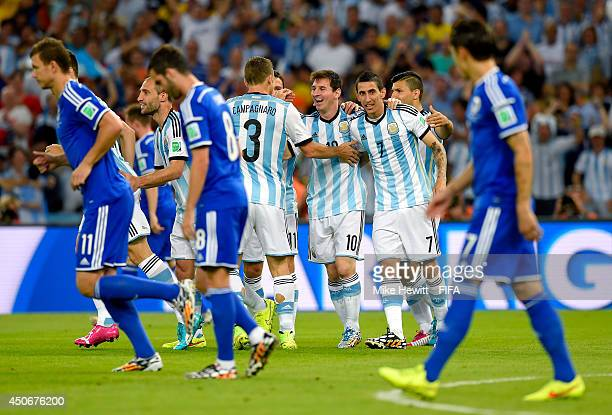 Lionel Messi of Argentina celebrates with teammates after Sead Kolasinac of Bosnia and Herzegovina scored an own goal during the 2014 FIFA World Cup...