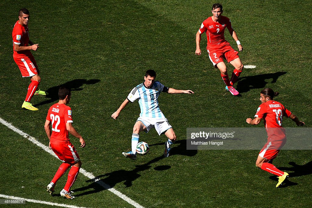 <a gi-track='captionPersonalityLinkClicked' href=/galleries/search?phrase=Lionel+Messi&family=editorial&specificpeople=453305 ng-click='$event.stopPropagation()'>Lionel Messi</a> of Argentina controls the ball against Josip Drmic (L), Fabian Schar (2nd L), <a gi-track='captionPersonalityLinkClicked' href=/galleries/search?phrase=Stephan+Lichtsteiner&family=editorial&specificpeople=709876 ng-click='$event.stopPropagation()'>Stephan Lichtsteiner</a> (2nd R) and <a gi-track='captionPersonalityLinkClicked' href=/galleries/search?phrase=Ricardo+Rodriguez+-+Soccer+Player&family=editorial&specificpeople=8768006 ng-click='$event.stopPropagation()'>Ricardo Rodriguez</a> of Switzerland during the 2014 FIFA World Cup Brazil Round of 16 match between Argentina and Switzerland at Arena de Sao Paulo on July 1, 2014 in Sao Paulo, Brazil.
