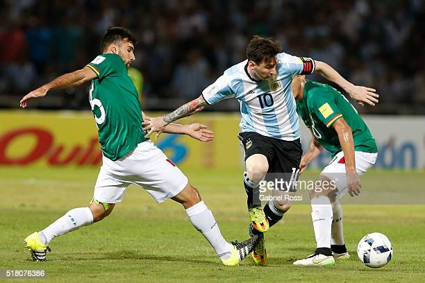 Lionel Messi of Argentina dribbles past Danny Bejarano and Jhasmani Campos of Bolivia during a match between Argentina and Bolivia as part of FIFA...