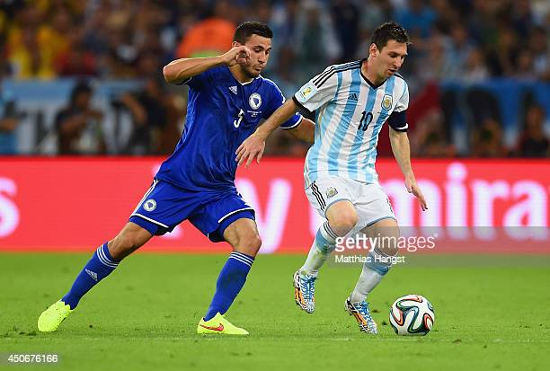 Lionel Messi of Argentina dribbles past Sead Kolasinac of Bosnia and Herzegovina during the 2014 FIFA World Cup Brazil Group F match between...