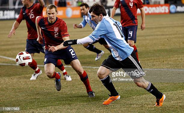 Lionel Messi of Argentina drives by Jonathan Spector of the United States during the first half of a friendly match at New Meadowlands Stadium on...