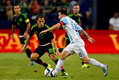 Lionel Messi of Argentina drives the ball as Andres Guardado of Mexico defends during a friendly match between Argentina and Mexico at ATT Stadium on...