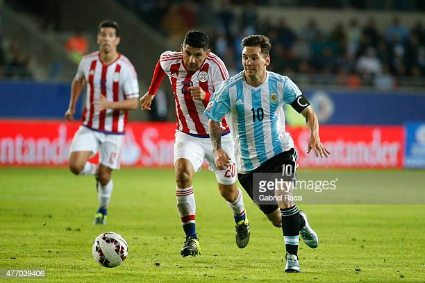 Lionel Messi of Argentina drives the ball while is followed by Nestor Ortigoza of Paraguay during the 2015 Copa America Chile Group B match between...
