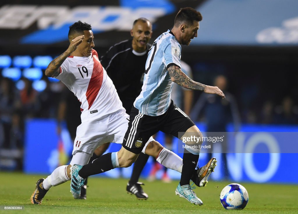 Lionel Messi of Argentina fights for ball with Victor Flores of Peru during a match between Argentina and Peru as part of FIFA 2018 World Cup Qualifiers at Estadio Alberto J. Armando on October 5, 2017 in Buenos Aires, Argentina.