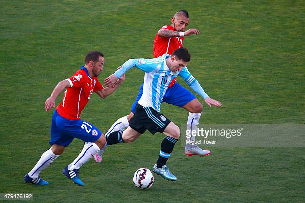 Lionel Messi of Argentina fights for the ball with Marcelo Diaz and Arturo Vidal of Chile during the 2015 Copa America Chile Final match between...