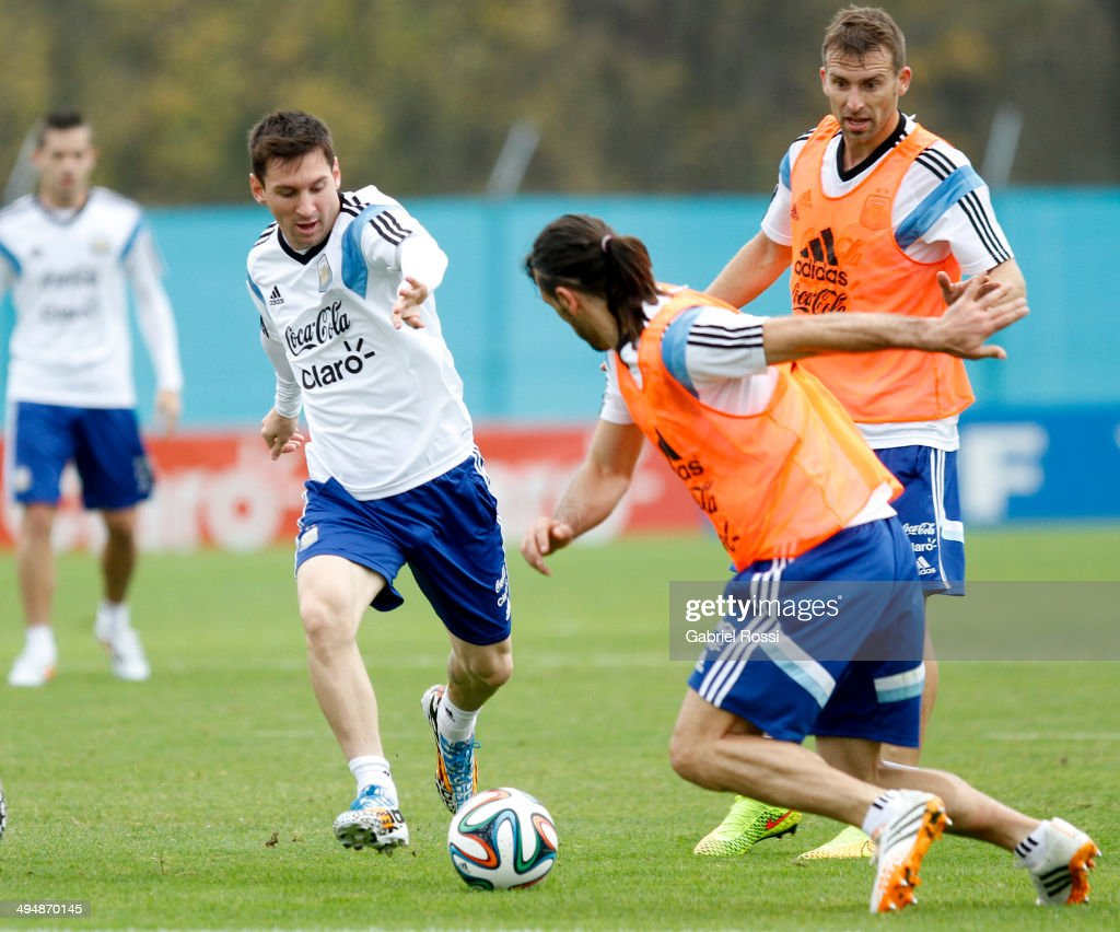 Lionel Messi of Argentina (L) fights for the ball with Martin Demichelis (M) as Hugo Campagnaro looks on during an Argentina training session at Ezeiza Training Camp on May 31, 2014 in Ezeiza, Argentina.