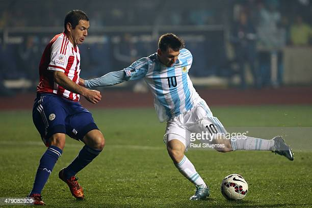 Lionel Messi of Argentina fights for the ball with Pablo Aguilar of Paraguay during the 2015 Copa America Chile Semi Final match between Argentina...