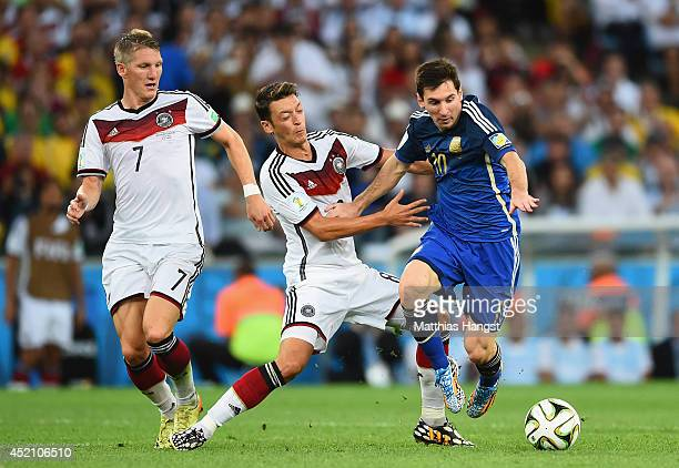 Lionel Messi of Argentina fights off Mesut Oezil of Germany during the 2014 FIFA World Cup Brazil Final match between Germany and Argentina at...