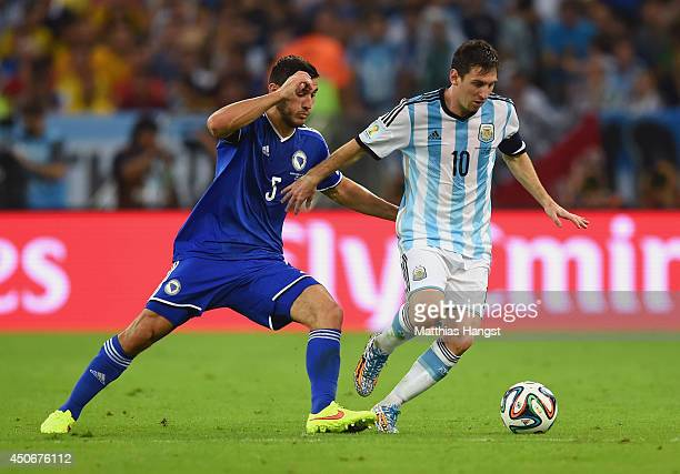 Lionel Messi of Argentina fights off Sead Kolasinac of Bosnia and Herzegovina during the 2014 FIFA World Cup Brazil Group F match between Argentina...