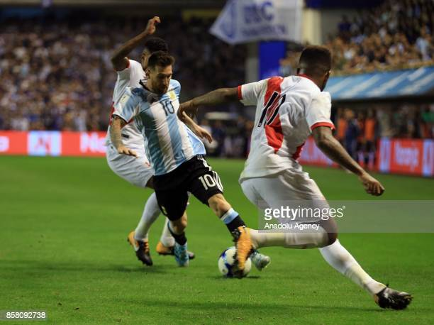 Lionel Messi of Argentina in action against Wilder Cartagena and Raul Ruidiaz of Peru during the 2018 FIFA World Cup Qualification match between...