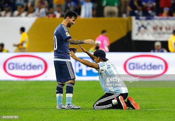 Lionel Messi of Argentina interacts with a fan who ran onto the field prior to the start of the second half during a 2016 Copa America Centenario...