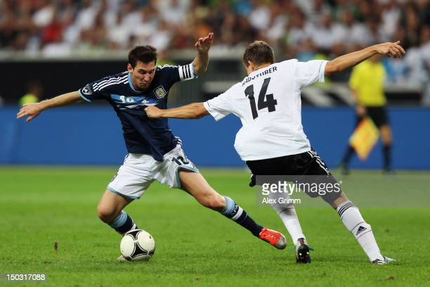 Lionel Messi of Argentina is challenged by Holger Badstuber of Germany during the international friendly match between Germany and Argentina at...