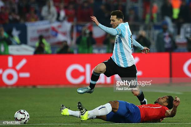 Lionel Messi of Argentina jumps over Jean Beausejour of Chile during the 2015 Copa America Chile Final match between Chile and Argentina at Nacional...