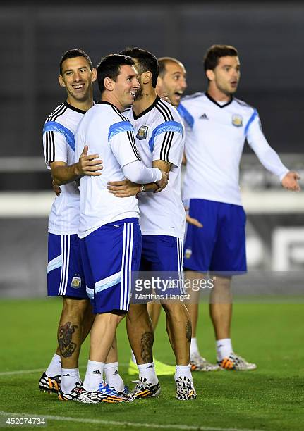Lionel Messi of Argentina shares a joke with teammates during the Argentina training session ahead of the 2014 FIFA World Cup Final at Estadio Sao...