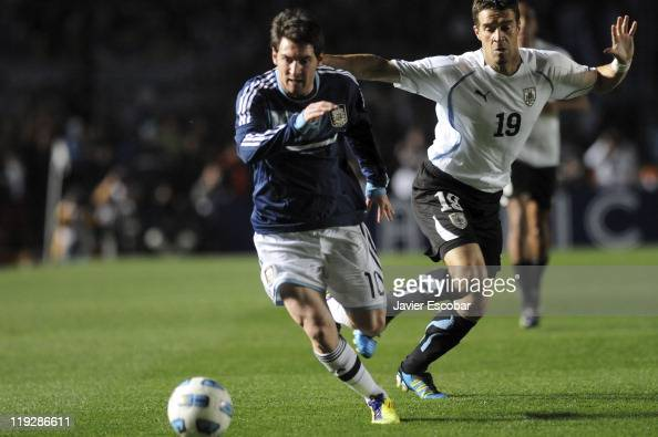 Lionel Messi of Argentina struggle for the ball with Andrés Scotti of Uruguay during the game between Argentina and Uruguay as part of the Cuarter...