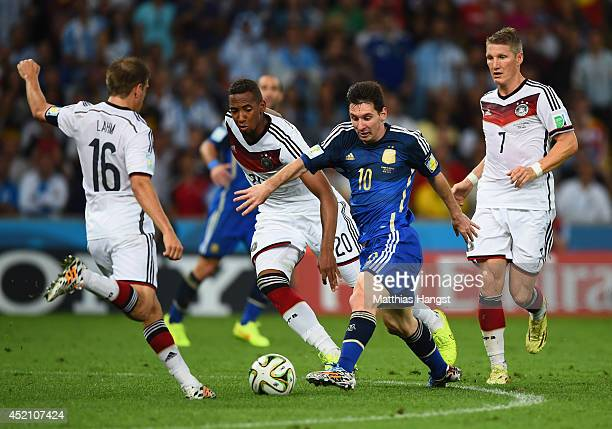 Lionel Messi of Argentina takes on Philipp Lahm and Jerome Boateng Germany during the 2014 FIFA World Cup Brazil Final match between Germany and...