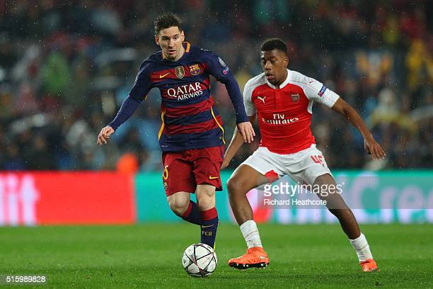 Lionel Messi of Barcelona and Alex Iwobi of Arsenal compete for the ball during the UEFA Champions League round of 16 second Leg match between FC...