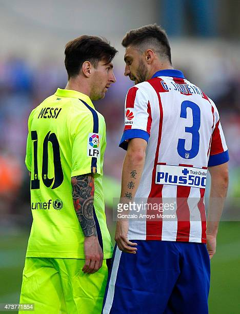 Lionel Messi of Barcelona and Guilherme Siqueira of Atletico Madrid clash during the La Liga match between Club Atletico de Madrid and FC Barcelona...