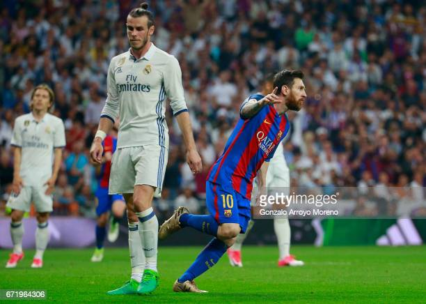 Lionel Messi of Barcelona celebrates as he scores their first and equalising goal as Gareth Bale of Real Madrid looks dejected during the La Liga...