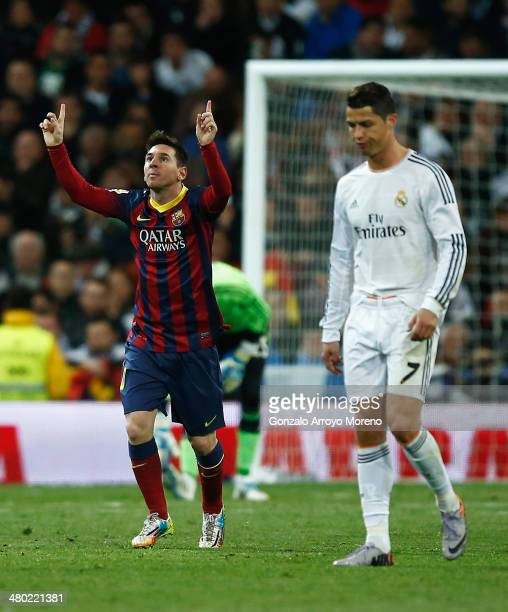 Lionel Messi of Barcelona celebrates scoring his team's third goal as Cristiano Ronaldo of Real Madrid looks dejected during the La Liga match...