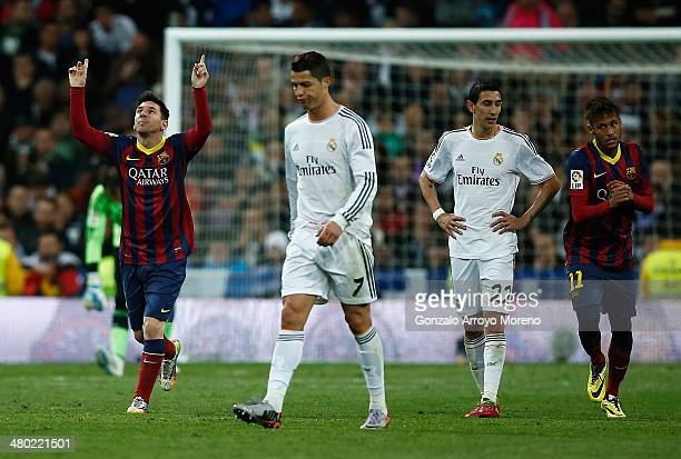 Lionel Messi of Barcelona celebrates scoring his team's third goal with Neymar of Barcelona as Cristiano Ronaldo and Angel Di Maria of Real Madrid...