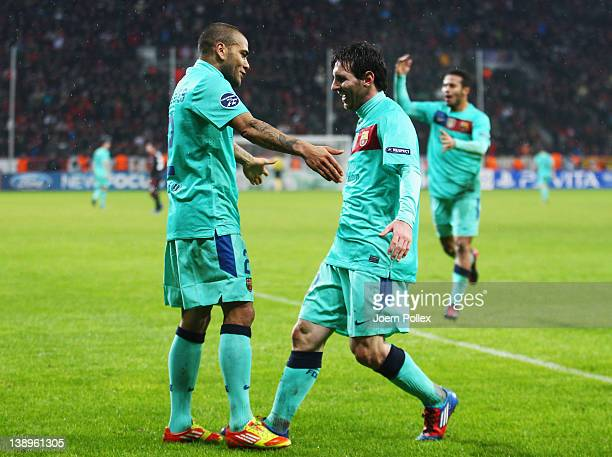 Lionel Messi of Barcelona celebrates with his team mate Dani Alves after scoring his team's third goal during the UEFA Champions League round of...