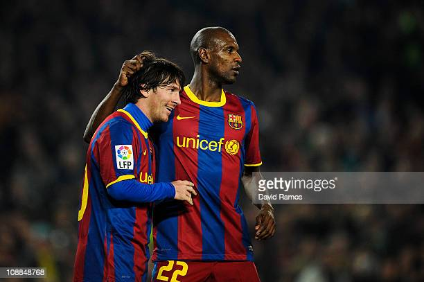 Lionel Messi of Barcelona celebrates with his teammate Eric Abidal after scoring his third goal during the La Liga match between Barcelona and...