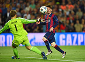 Lionel Messi of Barcelona chips the ball over goalkeeper Manuel Neuer of Bayern Muenchen to score his team's second goal during the UEFA Champions...