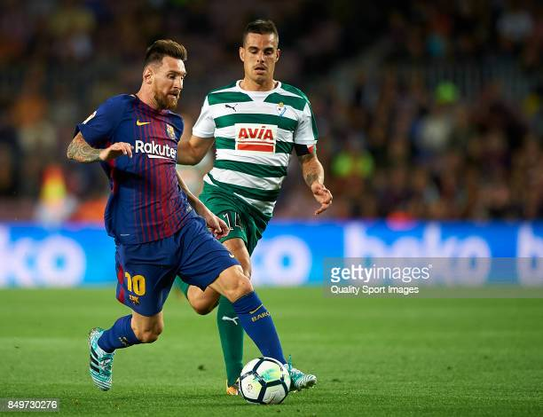 Lionel Messi of Barcelona competes for the ball with Dani Garcia of Eibar during the La Liga match between Barcelona and Eibar at Camp Nou on...