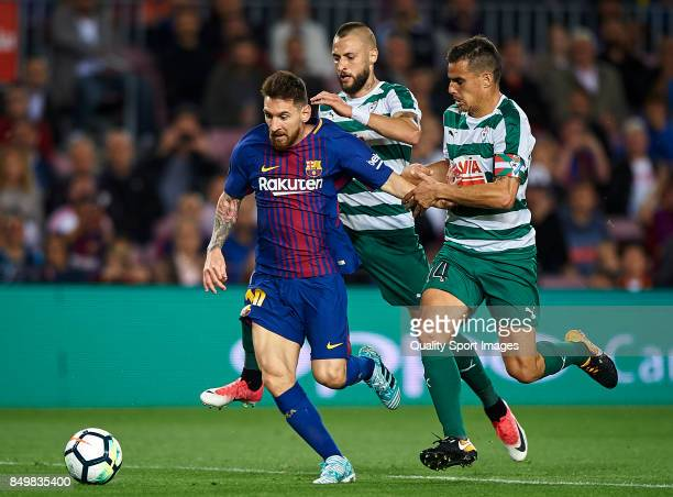 Lionel Messi of Barcelona competes for the ball with David Junca and Dani Garcia of Eibar during the La Liga match between Barcelona and Eibar at...