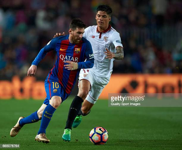 Lionel Messi of Barcelona competes for the ball with Joaquin Correa of Sevilla during the La Liga match between FC Barcelona and Sevilla FC at Camp...